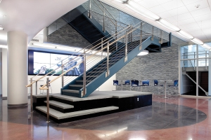 The lobby of the Lawrence and Sally Cohen Science Center offers a dramatic welcome, with a natural stone wall, large flat video screen and seating areas for students and visitors.