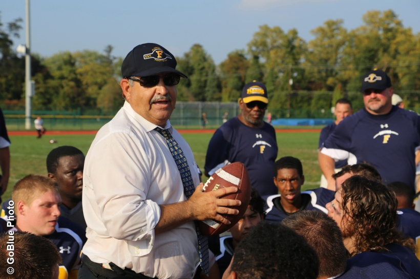 Joe Frappoli '69 meets with his players on the sidelines.  PHOTO COURTESY FLORENCE HIGH SCHOOL ATHLETICS